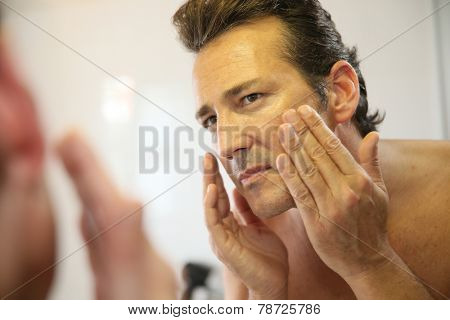 Middle-aged man in bathroom applying facial lotion