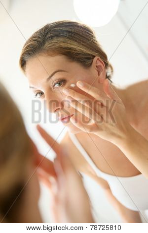 Middle-aged woman applying anti-aging cream