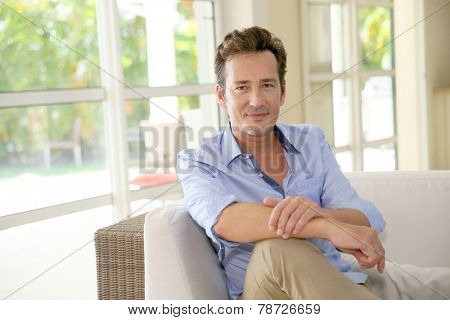 Portrait of single middle-aged man sitting in sofa
