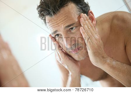 Handsome man rinsing face after shaving