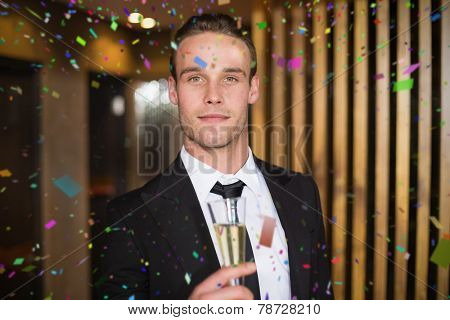 Handsome man holding flute of champagne against flying colours