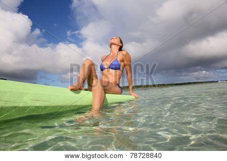 Beautiful woman with bikini posing sitted on canoe