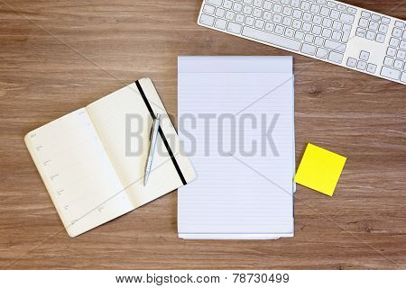 Background image wit assorted items, used for planning: a calendar, and notepad, pen, yellow sticky notes and a keyboard, on a wooden surface