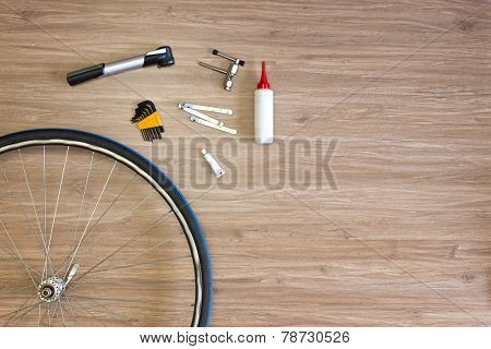 Background with bicycle tools laid out on a wooden floor, with a spoked wheel, tire levers, a pump, glue and a chain punch. Items, used to repair a flat tire