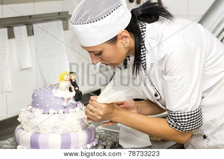 pastry chef decorates a cake
