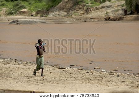 African Girl Goes On The River Bank
