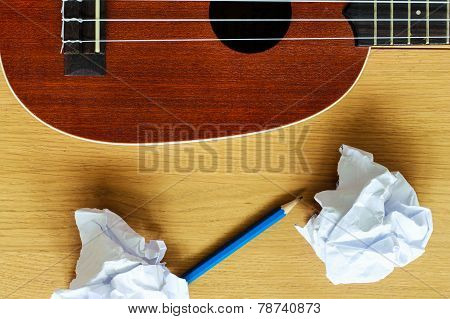 Ukulele Guitar With Paper Scraps And Pencil
