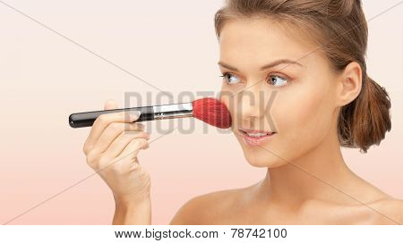 beuty, people and accessories concept - beautiful smiling woman with bare shoulders and make up brush over pink background