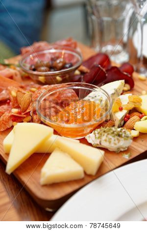 Cheese and sausage platter with nuts and citrus jam, copy space