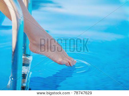 Slender female legs on the edge of the pool.