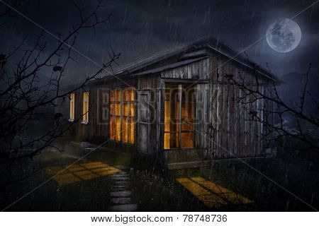 House With Glowing Windows At Night
