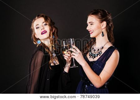 Two beautiful women in black cocktail dresses with glasses of champagne