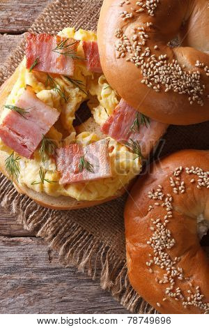Bagel With Egg And Bacon Close-up. Vertical View From Above