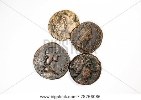 Four antique coins on a white background