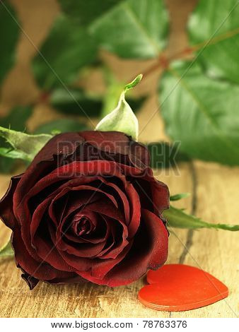 Red Rose And Red Heart On A Wooden Table.