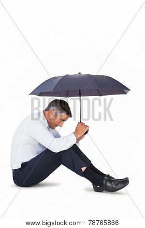 Businessman sitting and sheltering with umbrella on white background