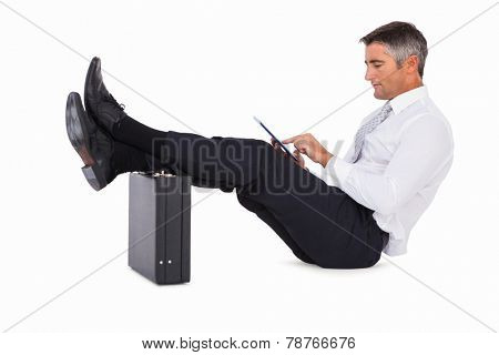 Businessman sitting with foot on briefcase and using tablet on white background