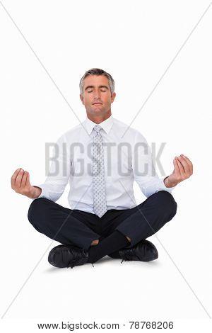 Zen businessman meditating in lotus pose on white background