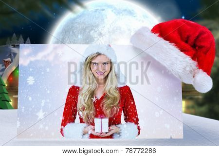 pretty girl in santa outfit holding gift against quaint town with bright moon