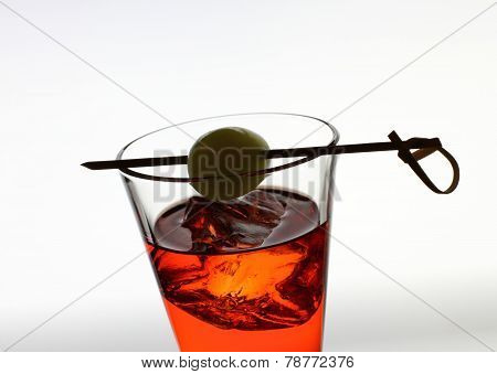 Short Drink Glass With Red Liquid, Olive, Ice Cubes