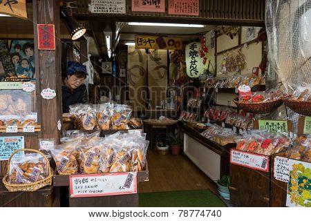 TAKAYAMA, JAPAN - DECEMBER 3, 2014: Vendors at their shop at the Miyagawa morning market in Takayama, Japan. This marketplace sells food items, groceries to farm produce and is common in rural Japan.