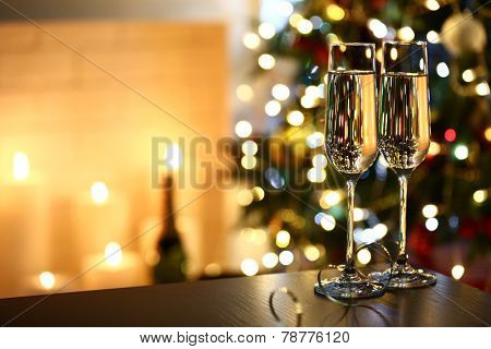 Two glass with champagne on table on Christmas tree and fireplace background