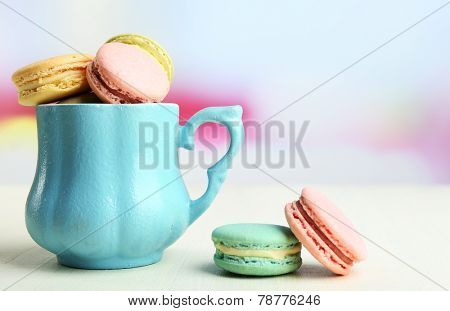 Assortment of gentle colorful macaroons in colorful mug on color wooden table, on light background