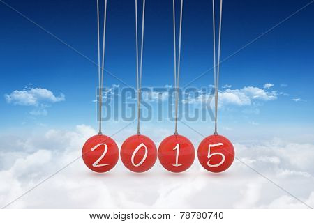 2015 newtons cradle against bright blue sky over clouds