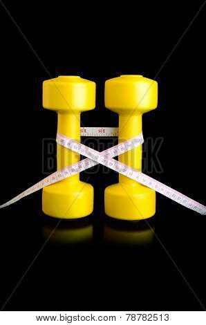 Two Yellow Dumbbells And Tape Measure Vertically On Black Background