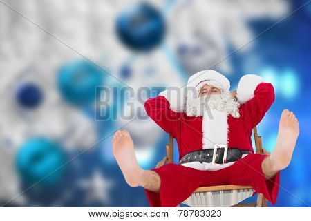 Relaxed santa stiting on deckchair against christmas decorations hanging from branch