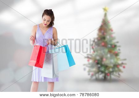 Stylish brunette in purpul dress opening shopping bag against blurry christmas tree in room