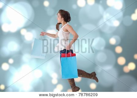 Happy brunette leaping with shopping bags against blurred lights