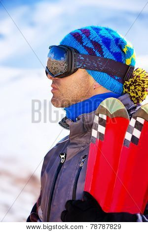 Handsome man enjoys alpine ski resort, portrait of a happy guy playing winter sports, tourist travel to Europe on Christmas holidays