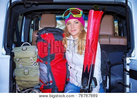 Happy girl enjoying winter sports, cheerful portrait of a woman sitting in the car and wearing ski mask, arrived to alpine ski resort, tourist travel on Christmas holidays