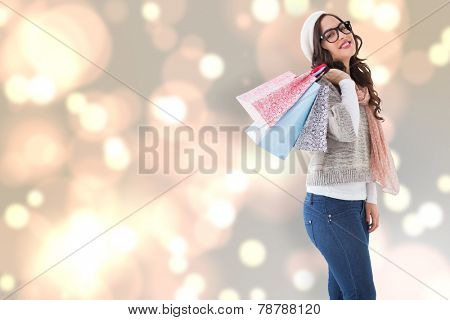 Brunette with glasses holding shopping bags against blurred lights