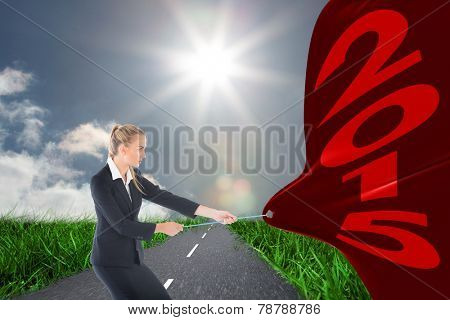 Focused blonde businesswoman pulling a rope against road on grass