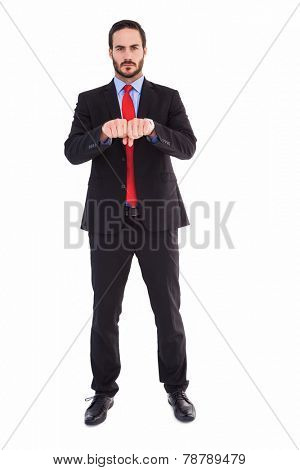 Unsmiling businessman with clenched fist in front of him on white background