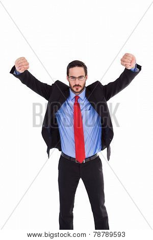 Unsmiling businessman standing with arms raised on white background