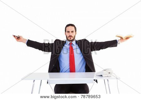Unsmiling businessman sitting with arms outstretched on white background