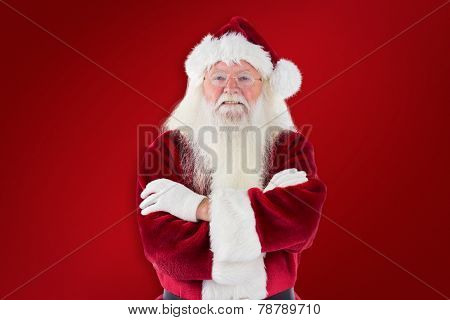 Santa smiles with folded arms against red background