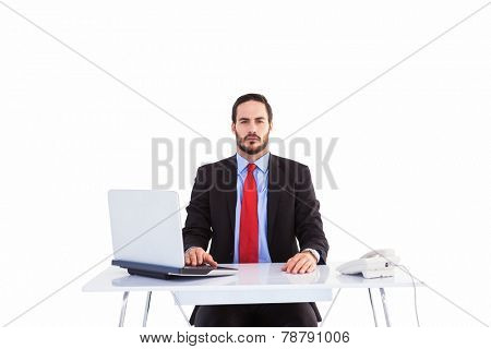 Unsmiling businessman sitting at desk on white background