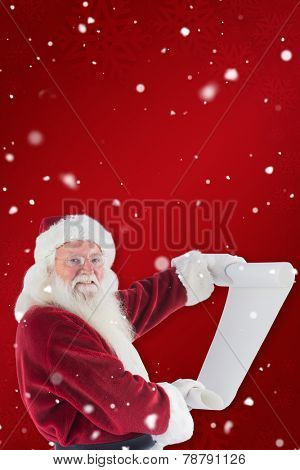 Father Christmas holds a list against red snowflake background