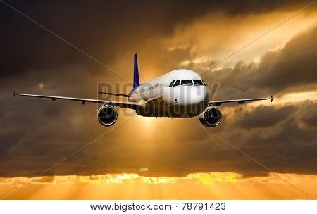 A Passenger Plane Flying In The Sky At Sunset
