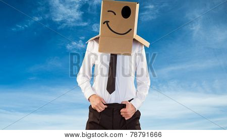 Anonymous businessman with hands in waistband against blue sky