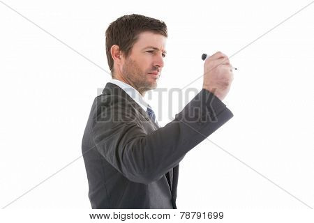 Serious businessman holding a marker and writing on white background