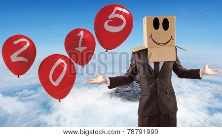 Anonymous businessman with hands out against mountain peak through the clouds