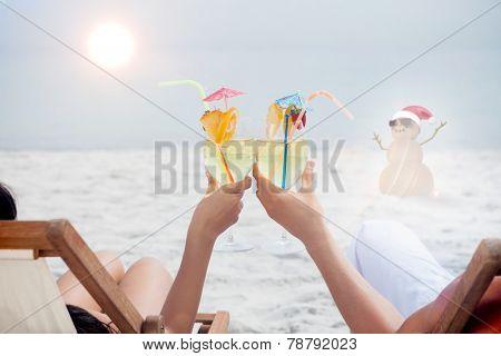 Couple clinking glasses of cocktail on beach against festive sandman