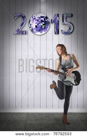 Pretty young girl playing her guitar against grey room