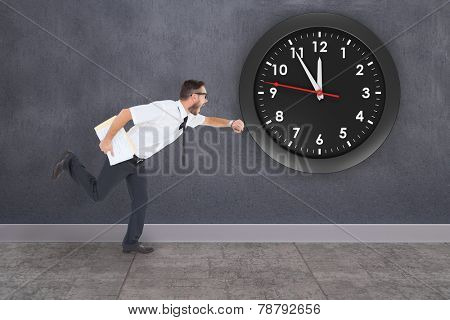 Geeky young businessman running late against grey room