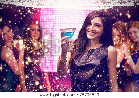 Brunette with cocktail against gold and red lights